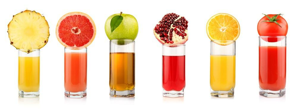 Various glasses of fruit and vegetable juices with the main ingredient placed on the rim of the glass.