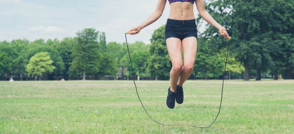 Fit woman using a jump rope in a park.