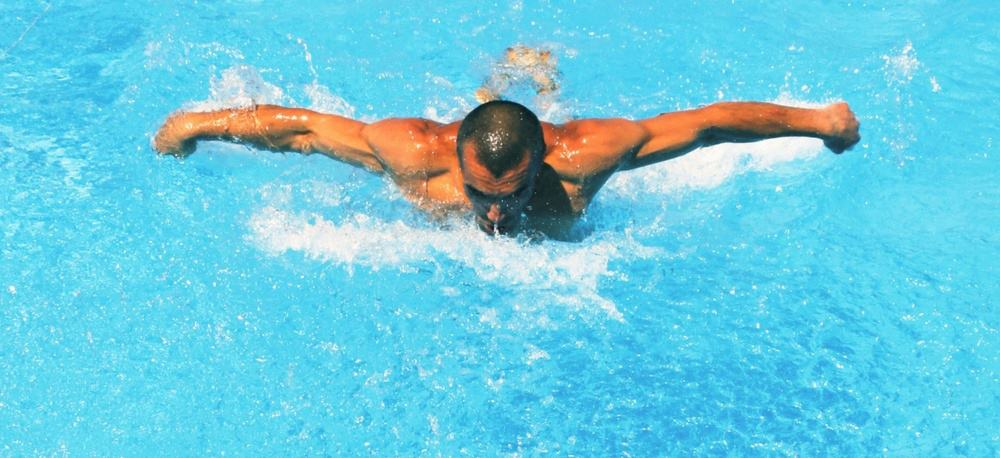 A man doing butterfly strokes in a swimming pool.