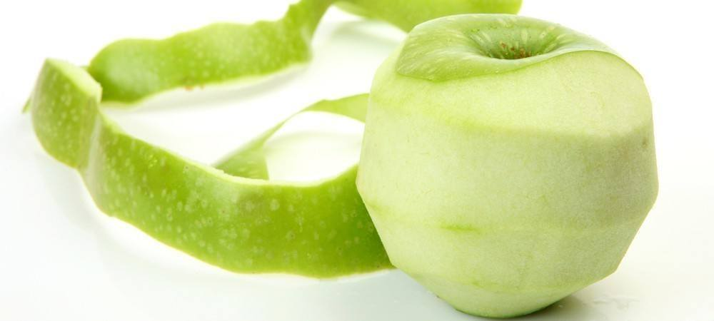 A green apple with it's peel placed next to it.