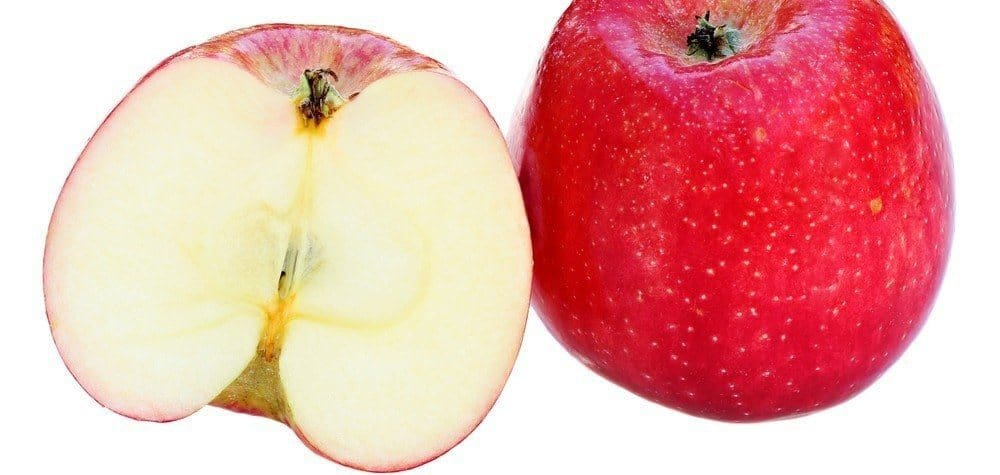 A red apple cut in half and two halves placed next to each other, with one facing the camera.