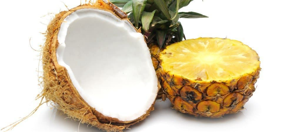 A coconut shell and half of a pineapple.