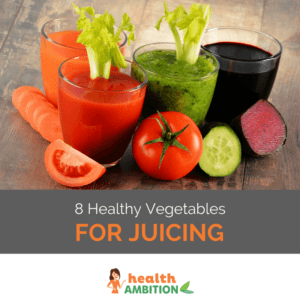 """Glasses of vegetable juice surrounded by vegatables like a slice of tomato, beetroot and a carrot; the title says """"8 Healthy Vegetables for Juicing."""""""