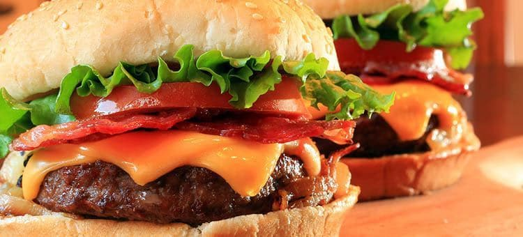 Two juicy burgers with cheese and vegetables.