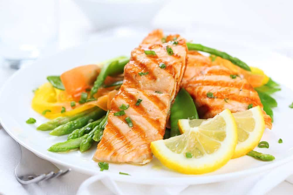 Two slices of grilled salmon tastefully presented on a plate with slices of lemon and vegetables.