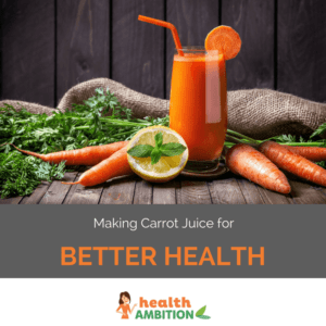 A glass of carrot juice with a straw next to lime, leaves, and carrots.