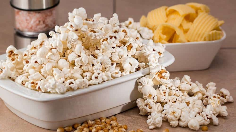 A bowl of popcorn next to chips.