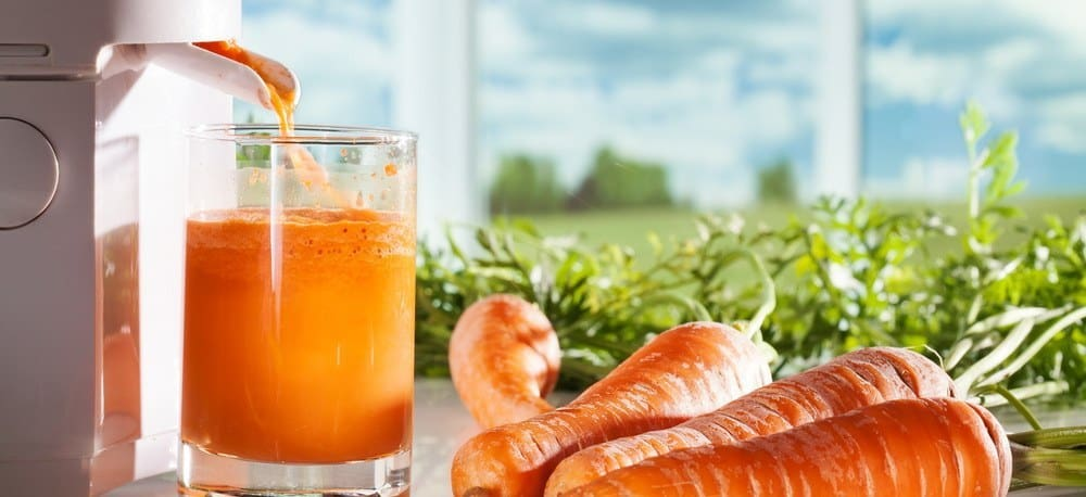 A glass of carrot juice in the process of being extracted using a juicer, next to a few carrot sticks.