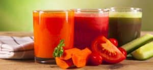 Three glasses of vegetable juice next to a slice of tomato and some carrots and cucumber.