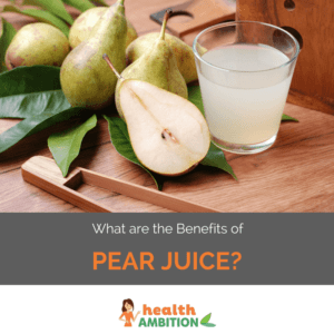 A glass of pear juice next to pears.