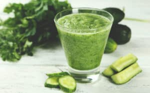 Cucumber juice with all its benefits surrounded by sluices of cucumber on white wooden table.
