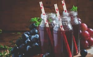 Three glasses of grape juice with straws, getting its benefits from grapes like the ones around it.